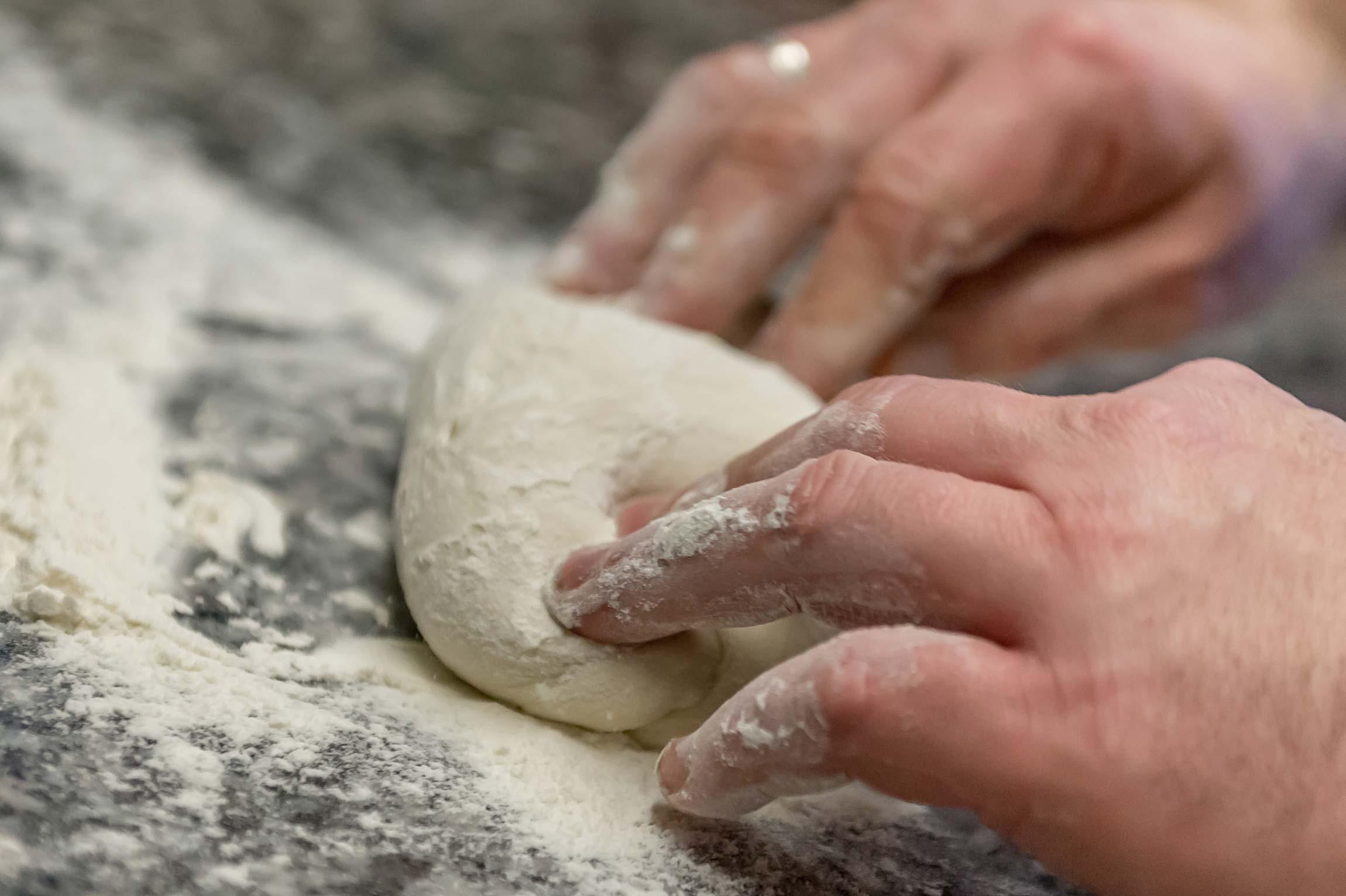 Mehlige Hände kneten Pizzateig