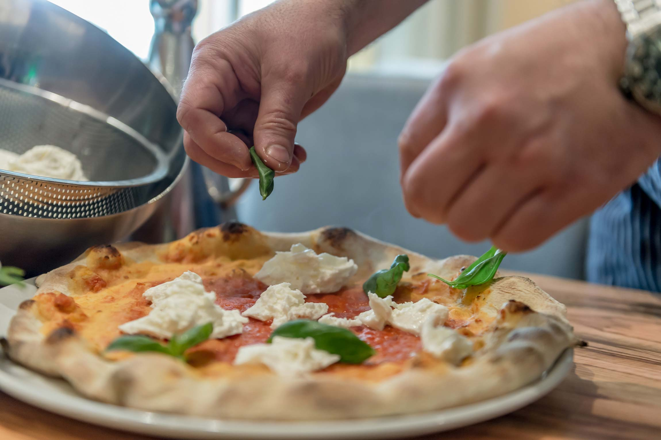 Fertige Pizza wird mit Basilikumblättern bestreut