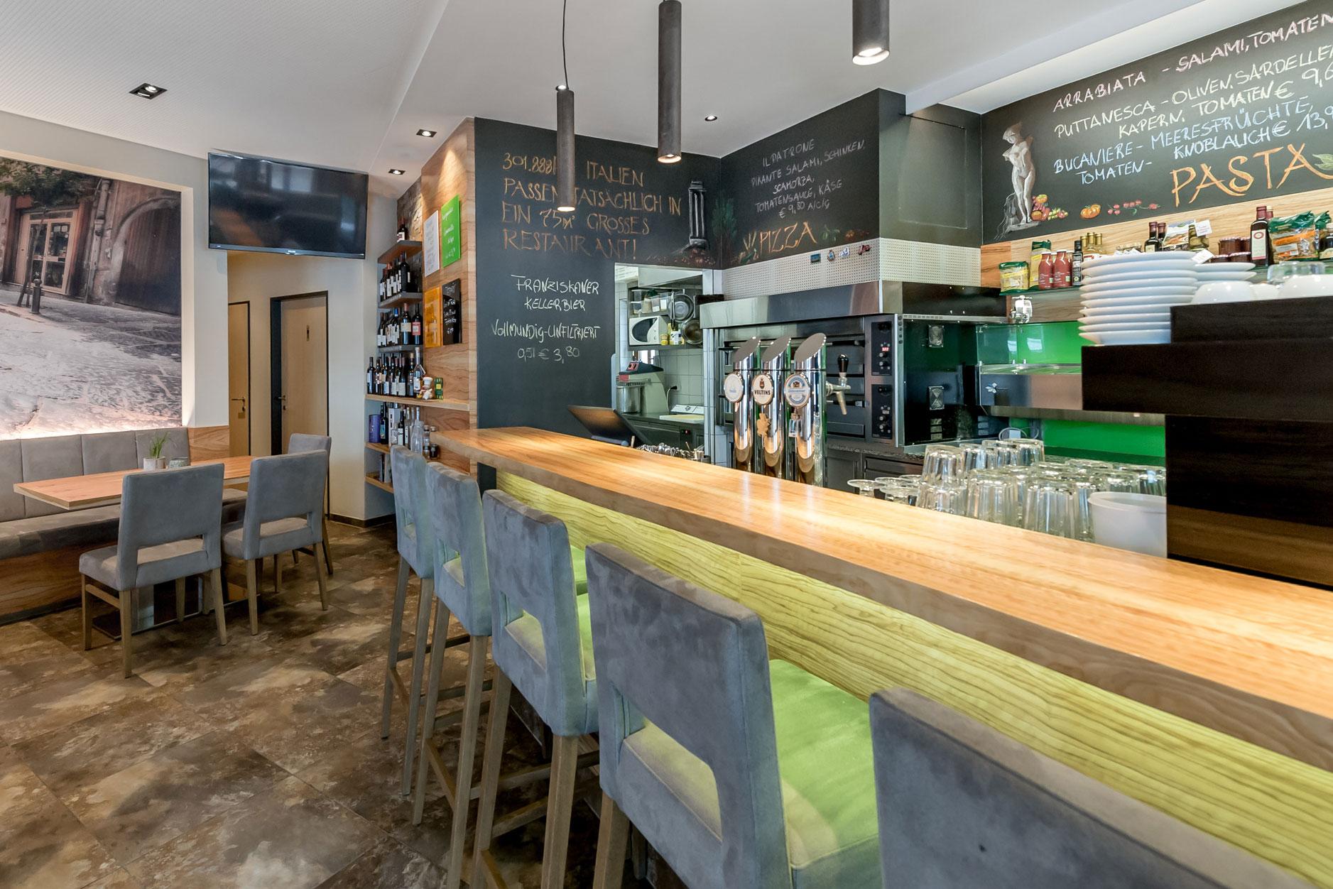Bar mit Hockern, Zapfsäulen, Pizzaofen und Lebensmitteln
